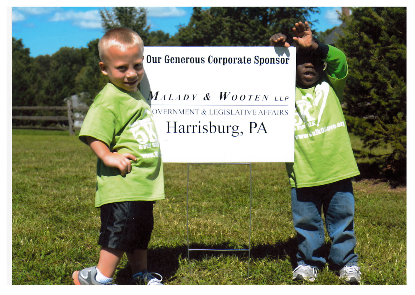 two young boys standing next to a sign that thanks Malady & Wooten government & legislative affairs for their corporate sponsorship